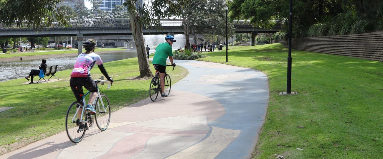 Two cyclists on the cycle path alongside Parramatta River
