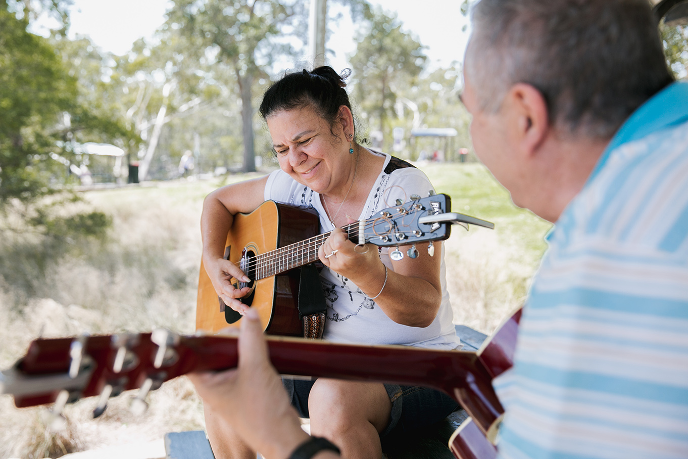 Woman and man playing guitar at Lake Parramatta