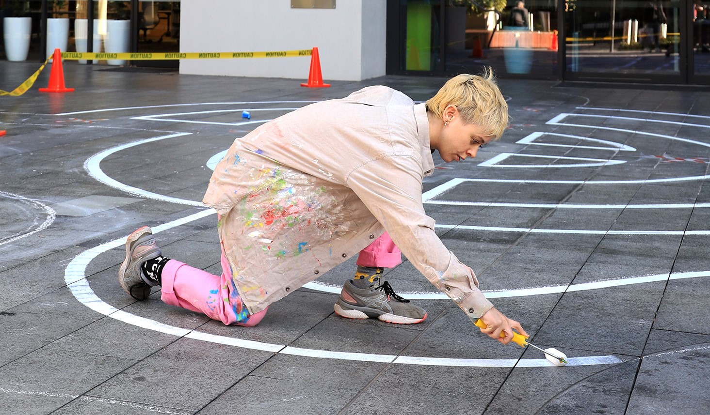 Nadia Odlum painting a labyrinth painting at the Wentworth Point Community Centre and Library forecourt.