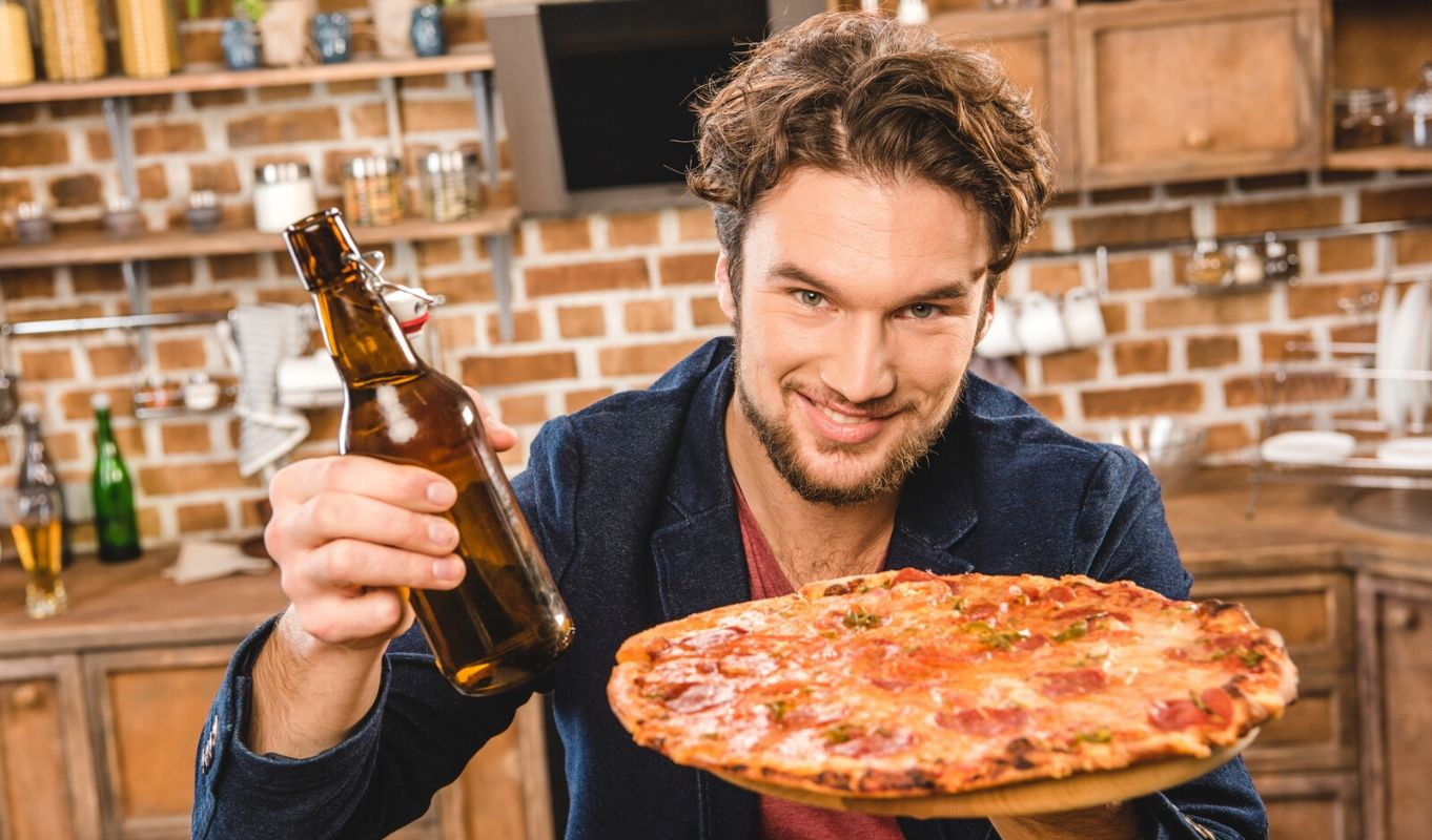 Young man offers pizza and a bottle of beer