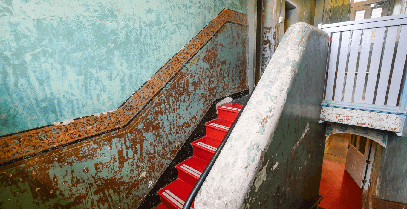 the interior stairwell of Female Orphan School with red steps and white balistrade