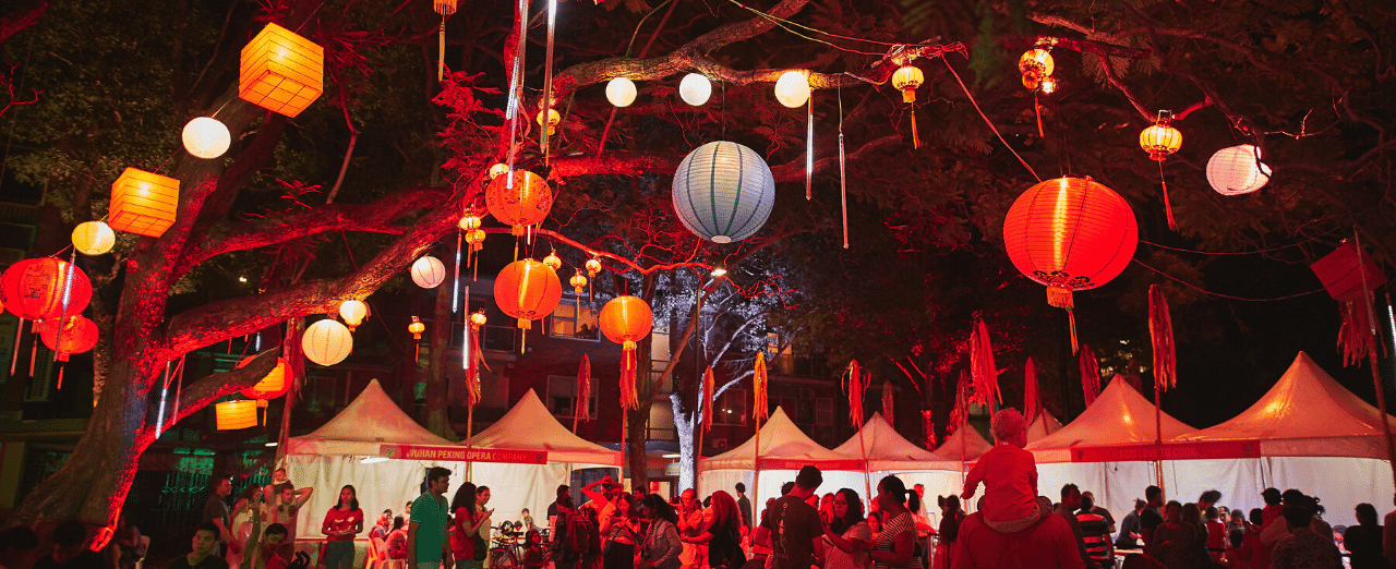 a night time festival scene with lanterns, lights and stalls
