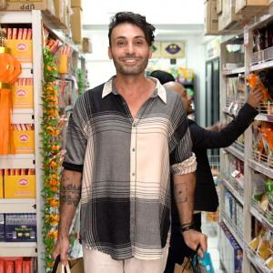 Man standing in Radhe grocery holding shopping bags