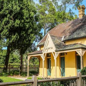 a single-storey colonial cottage with picket fence in Parramatta Park