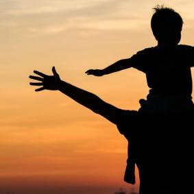 picture of a dad with his kid on his shoulders facing the sunset, both with their arms outstretched.