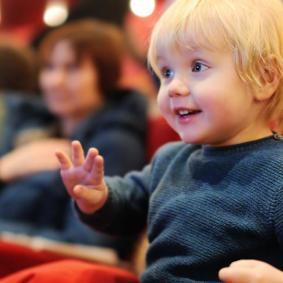 Small blonde haired boy sat in theatre with delighted expression on his face