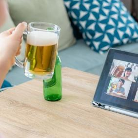 Young woman toasts her laptop screen with beer in a glass tankard, pizza on the table by her side