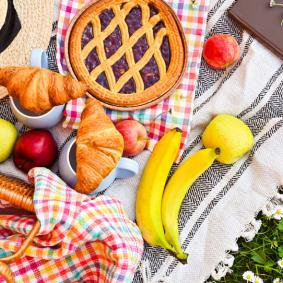 Picnic blanket and basket with pie and summer hat on grass