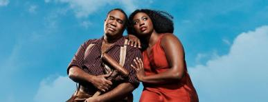 a male and female African American actor holding each other with blue sky backdrop
