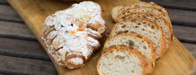 photo of fresh sliced bread and croissant on wooden serving board