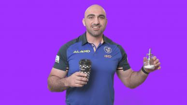 Tim Mannah holding a sugar canister and disposable coffee cup