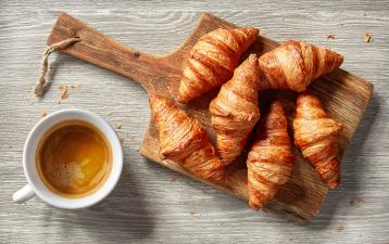 croissants on bread board with coffee