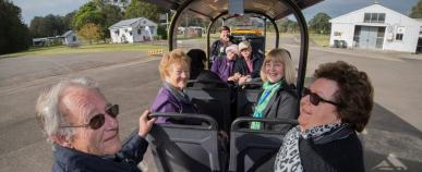 a group of older people in a trolley tour bus at Newington Armory