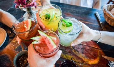 close up image of four people holding cocktails gesturing 'Cheers'