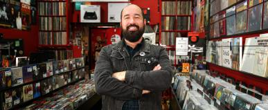Owner of Beatdisc Records Pete stands in his record store with a big smile on his face