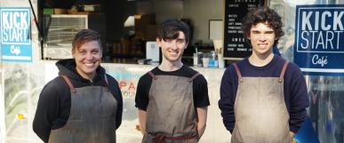 Three Kick Start trainees standing in front of Kick Start food truck