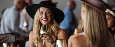 women talking and drinking out of golden wine glasses dressed in their fabulous race day outfits