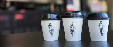 three takeaway coffee cups in a row