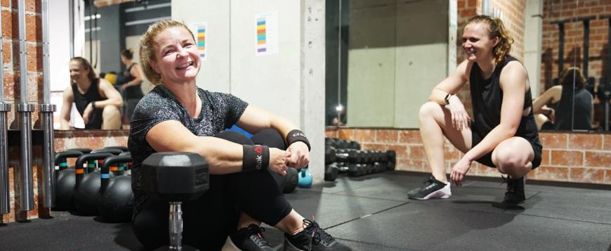 Two women smiling in a gym with weights nearby